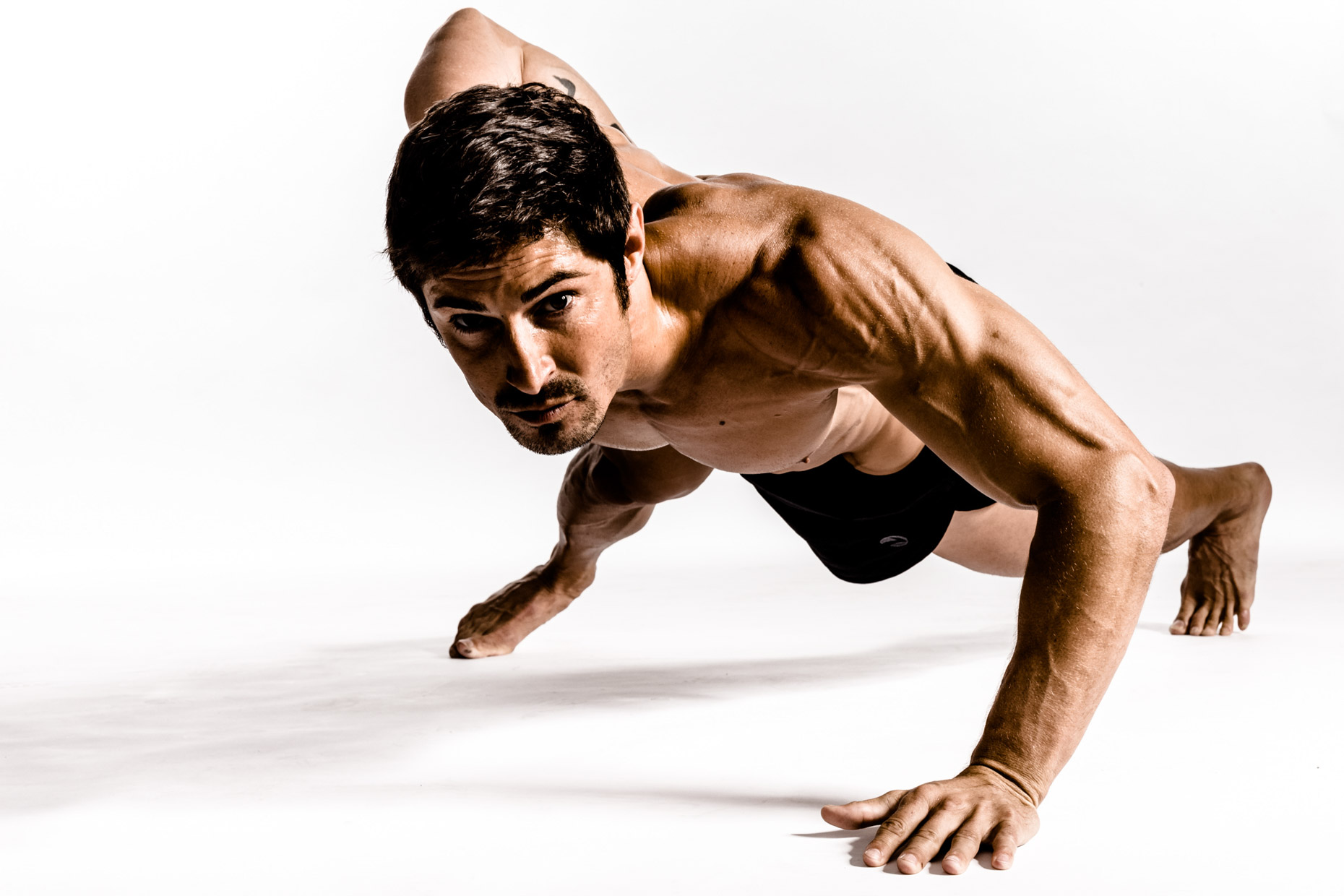 Rudy Reyes performs push ups for dramatic fitness photographer Andy Batt
