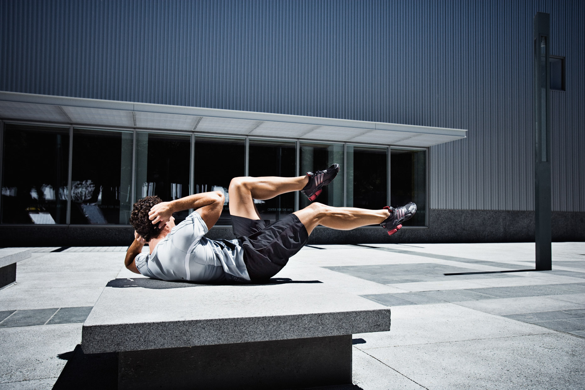 crossfit training and stretching sit ups in urban San Francisco by dramatic fitness photographer Andy Batt
